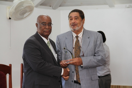 Leader of the Opposition Hon. Joseph Parry receiving a plaque from Deputy Governor General His Honour Eustace John from the Nevis Island Assembly as one of the longest serving parliamentarian at a special sitting of the Assembly on December 10, 2013 at the at its Chambers in Hamilton House