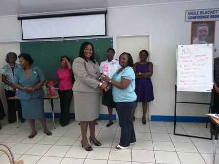 President of the Nevis National Women's Council Ms. S. Patricia Claxton receives a token from Assistant Secretary in the Ministry of Social Development Ms. Michelle Liburd while other members of the Council look on