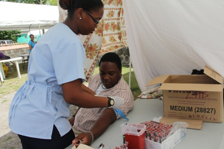 A member of the public getting tested on Voluntary Counseling and Testing (VCT) Day in 2012 by a Lab Technician from the Alexandra Hospital on Nevis
