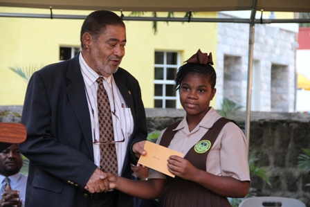 Deputy Governor General His Honour Eustace John presents Alexander Hamilton Scholarship package to Ms. Clarisa Dore of the Gingerland Secondary School