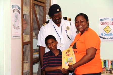 Manager of Caribbean Cable Communications Mrs. Trecia Daniel, officially handing over the books to one of the children at the Creative Youth Academy at the old Cotton Ground Police Station on December 23, 2014 while volunteer at Creative Youth Academy Mr. Joseph Williams looks on