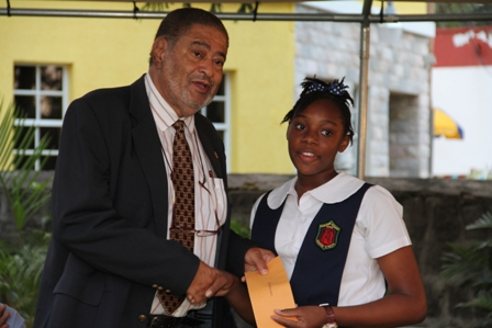 Deputy Governor General His Honour Eustace John presents Alexander Hamilton Scholarship package to Ms. Kyla Seabrookes of the Charlestown Secondary School