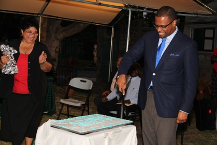Acting Premier of Nevis Hon. Mark Brantley cuts a birthday cake at the Happy Birthday Alexander Hamilton ceremony on the grounds of the Alexander Hamilton Museum on January 10, 2014 while Mrs. Evelyn Henville Executive Director of the Nevis Historical and Conservation Society looks on