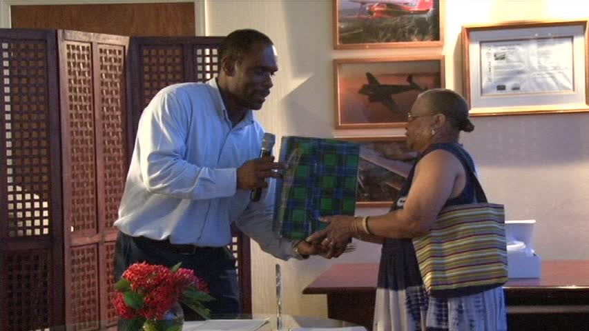 "Chairman of the Nevis Air and Sea Ports Authority Mr. Collin Dore presents retiree Ms. Elvira ""Fairy"" Clarke with a plaque and gift"" for her 22 years of service at the Vance W. Amory International Airport on December 30, 2013"