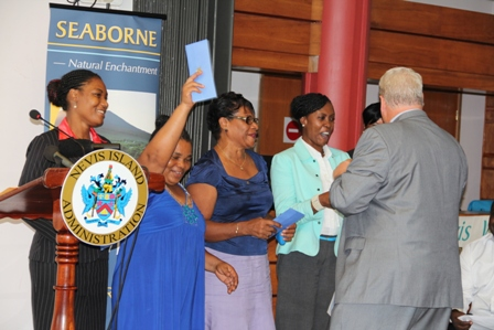 Director of Business Development with Seaborne Airlines Michael Ritzi hands out free tickets to five unsuspecting members of the public for trips to and from San Juan at a ceremony at the Vance W. Amory International Airport on January 22, 2014, to commemorate the inaugural flight of Seaborne Airlines into Nevis on January 15, 2014