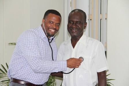 (L-R) Deputy Premier of Nevis and Minister of Health Hon. Mark Brantley in a light moment at his Bath Plain office on February 17, 2014, tests a stethoscope from a donation of medical supplies from the Global Faith Alliance through a partnership with Pastor Davidson Morton of the Eden Browne Church of God at Butlers Village, Nevis