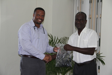 (L-R) Deputy Premier of Nevis and Minister of Health Hon. Mark Brantley receives medical supplies at his Bath Plain office on February 17, 2014, from Global Faith Alliance through a partnership with Pastor Davidson Morton of the Eden Browne Church of God at Butlers Village, Nevis