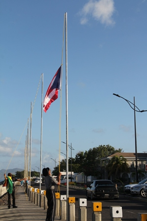 An officer of the Royal St. Christopher and Nevis Police Force hoisting the flags at the Charlestown Waterfront on February 14, 2014. He is assisted by Devon Liburd Director of Sales and Marketing at the Nevis Tourism Authority