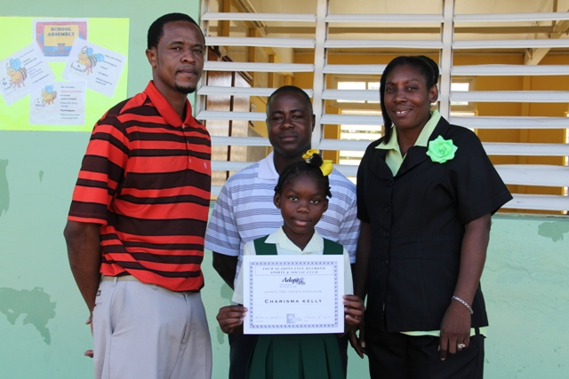 Ignacio Ottley Vice President the Four Seasons Five Diamond Sports and Social Club, Club President Lavorn Lawrence and Mrs. Janice Richards Principal of the Ivor Walters Primary School with the Four Seasons Five Diamond Sports and Social Club scholarship recipient Charisma Kelly