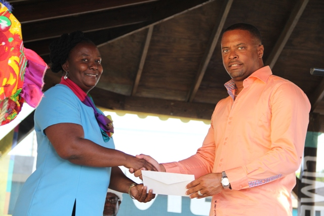 Deputy Premier and Minister of Culture on Nevis, Hon. Mark Brantley accepts $250,000 donation from Lornette Powell, representative of LIME, the platinum sponsor for Culturama 40