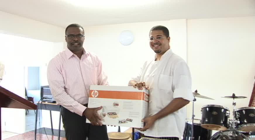 Deputy Premier of Nevis and Ministry of Health Hon. Mark Brantley presents computer system to Master Chef Michael Henville at the Charlestown Primary School's assembly on March 03, 2014