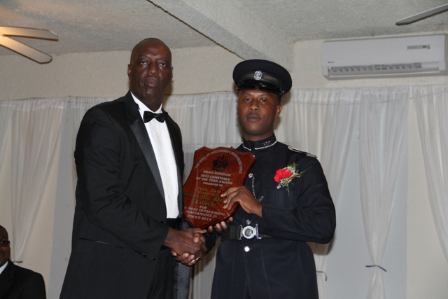 Commissioner of the Royal St. Christopher and Nevis Police Force Celvin Walwyn hands over the plaque to Constable of the Year for 2013 Rohan Laborde at the Police Constable Awards Ceremony and Dinner at the Occasions Entertainment Arcade on March 01, 2014