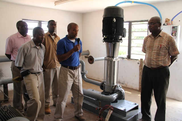 Manager of the Nevis Water Department, Roger Hanley (with the mike) with Electrical Technicians Clyshawn Wilson (front left) and Gavin Walters (back right), Assistant Secretary in the Ministry of Communication and Works and Public Utilities Denzil Stanley (back left) and Permanent Secretary in the Ministry of Communication and Works and Public Utilities Ernie Stapleton with the newly installed booster pump at the Fothergills Water Pumping Station on March 07, 2014