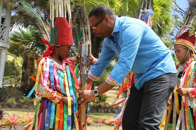 Deputy Premier and Minister of Culture, Hon. Mark Brantley, passes the Queen's Baton to a Nevisian masquerade dancer