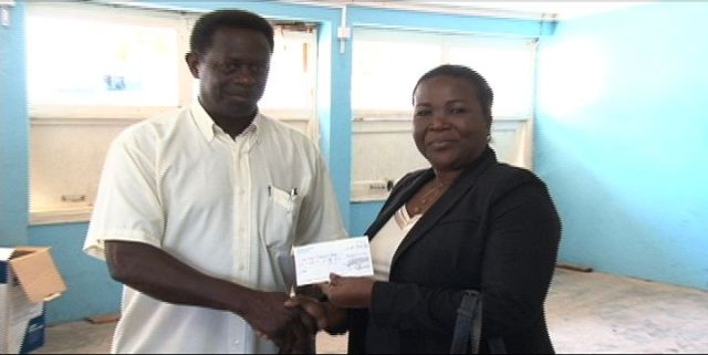 Chairman of UK-based St. Kitts/Nevis & Friends Association, Randolph Charles, hands over a cheque of £600 to Permanent Secretary in the Ministry of Education, Lornette Queeley-Connor at the Charlestown Secondary School on March 26, 2014