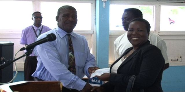 Permanent Secretary in the Ministry of Education Lornette Queeley-Connor hands over a cheque of £600 donated by the UK-based St. Kitts/Nevis & Friends Association to Principal of the Charlestown Secondary School Edson Elliott at the Charlestown Secondary School on March 26, 2014