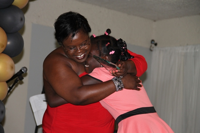Ms. Husaene Martin gets a heart-warming hug from Junior Minister for Youth and Sports in the Nevis Island Administration Hon. Hazel Brandy-Williams before she is presented with an award in the Minister's name at the Department of Youth and Sports Awards Ceremony and Gala on April 26, 2014 at the Occasions Conference Centre at the Pinney's Industrial Site