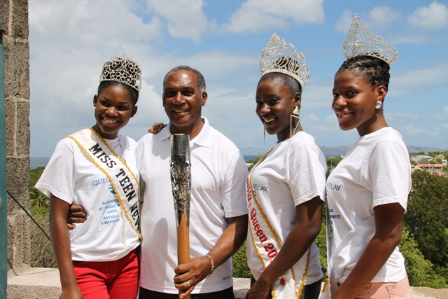 Premier of Nevis Hon. Vance Amory, Miss Teen Nevis Irveeka Nisbett, Miss Culture Jomelle Elliott and Miss Culture Swimwear Cherissa Maynard display Queen's Baton at the Apron of the Nevis Island Administration Building at Bath Plain
