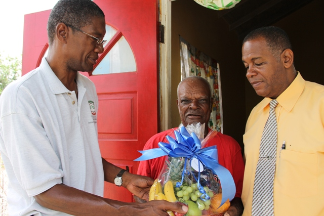 Ashley Webbe is presented with a fruit basket at his home in Middle Works, Hanley's Road, from the Director of the Department of Agriculture Keithley Amory (left) and Permanent Secretary in the Ministry of Agriculture Eric Evelyn (right) on Nevis for his contribution to the development of agriculture on Nevis as part of Agriculture Awareness Month