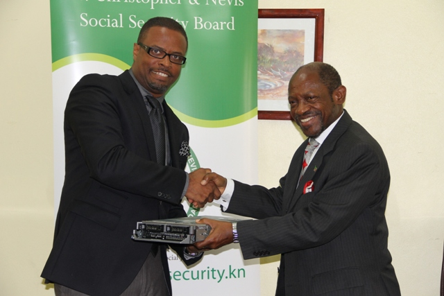 Acting Premier of Nevis Hon. Mark. Brantley (left) receives computer equipment for use by the Ministry of Finance from Prime Minister of St. Kitts and Nevis the Rt. Hon. Dr. Denzil Douglas through the St. Christopher and Nevis Social Security Board at a handing over ceremony at the Ministry of Finance conference room on May 22, 2014