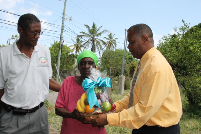 Director of the Department of Agriculture Keithley Amory (right) and Permanent Secretary in the Ministry of Agriculture on Nevis Eric Evelyn present a fruit basket to retired Agriculture Worker Claudina Claxton of Brown Hill on May 21, 2014, in appreciation of her contribution to the development of agriculture on Nevis as part of Agriculture Awareness Month