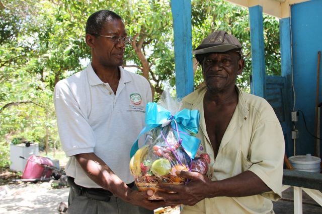 Agriculture retiree Rodrick Griffin being presented with a fruit basket as a token of appreciation for his contribution to the development of agriculture on Nevis at his home in Butlers, from the Department and Ministry of Agriculture from Director of Agriculture Keithley Amory as part of Agriculture Awareness Month