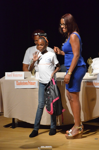 Vice President of the Nevis Association of South Florida Avonelle Hanley presents bag packs to Richonne Westerman of the Charlestown Primary School and other participants of the 2014 Warner's One Stop Family Book Feud