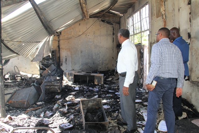 Members of the Nevis Island Cabinet looking at the burnt out Treasury Building