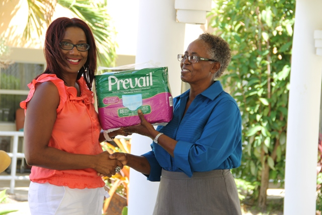 Vice President of the Nevis Association of South Florida, Avonelle Hanley officially handing over a donation of adult protective underwear to the Supervisor of the Flamboyant Nursing Home, Ena Sutton at the Flamboyant Nursing Home on May 19, 2014