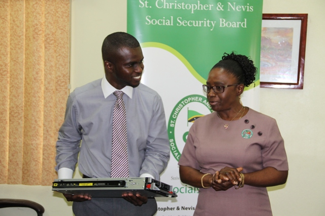 Head of the Information Technology Department in the Nevis Island Administration Quincy Prentice (L) with Director of the St. Christopher and Nevis Social Security Mrs. Sephlin Lawrence at the Ministry of Finance Conference room on May 22, 2014, during a handing over ceremony of server equipment for the Ministry of Finance from the Social Security Board