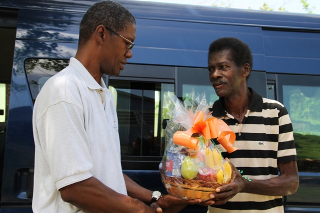 "Agriculture retiree Euclid ""Judge"" Saddler is presented with a fruit basket at his home in Brown Hill, from Director of the Department of Agriculture Keithley Amory on behalf of the Department and Ministry of Agriculture in the Nevis Island Administration for his dedicated contribution to agriculture on Nevis as part of Agriculture Awareness Month"