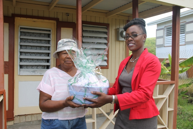 Director of the Nevis Investment Promotion Agency Kimone Moving presents a gift basket from NIPA and the Nevis Financial Services Department to Govanie Ward for her mother Selena Ward in Camps, who is the oldest person in the St. James' Parish