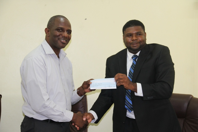 Chief Executive Officer of the St. Kitts and Nevis Sugar Industry Diversification Foundation Mr. Terrence Crossman (left) presenting the first payment from a grant for the Nevis Water Supply Enhancement Project jointly funded by the Caribbean Development Bank and the Administration, to Junior Minister in the Nevis Island Administration Troy Liburd on June 24, 2014 at the Ministry of Finance conference room