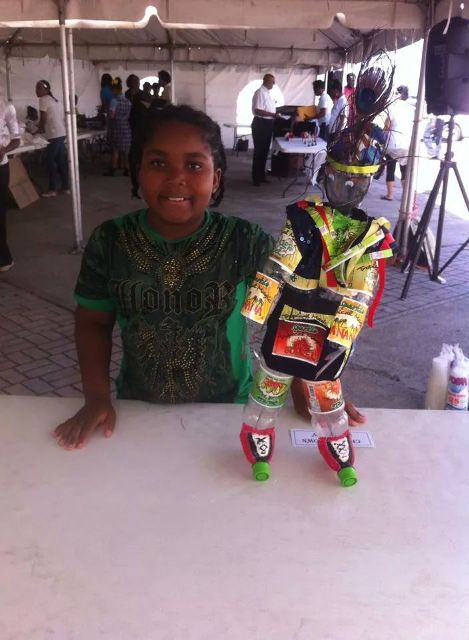 The first place winner in the St. Kitts Bottling Company Ltd. art competition Kaylan William of the Charlestown Primary School with her art project made of recyclable materials from Sparkle soda bottles