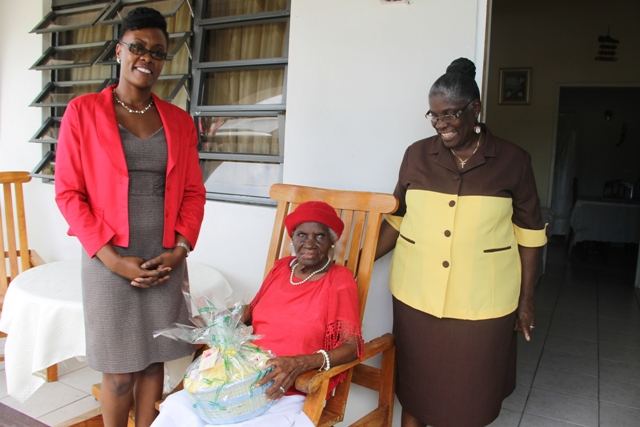 Director of the Nevis Investment Promotion Agency Kimone Moving with Alice Nisbett (seated) and her daughter Muriel St. Jean at Nisbett's home in Cotton Ground. Nisbett, the oldest person in the St. Thomas' Parish, was presented with a gift basket from NIPA and the Nevis Financial Services Department on June 17, 2014