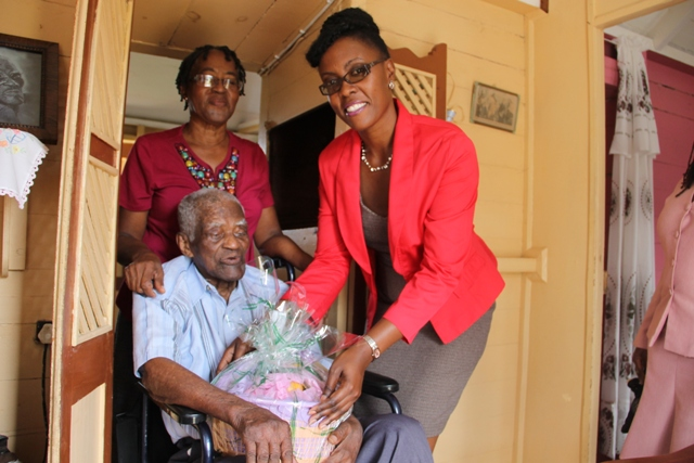 Director of the Nevis Investment Promotion Agency Kimone Moving presents a gift basket from NIPA and the Nevis Financial Services Department to Herman Ward, the oldest person in the Parish of St. Georges', at his home in Morning Star. Looking on is his daughter Hyleta Liburd