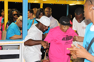 Members of The UK Invasion, a group from England visiting Nevis for the Homecoming Celebrations and Culturama 40 Celebrations disembark from the MV Prince Devonte J at the Charlestown Pier on Nevis on the evening of July 29, 2014