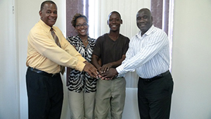 (L-R) Permanent Secretary in the Ministry of Agriculture on Nevis Eric Evelyn, Earth University scholarship holders Devene Smithen and Prince Arrindell with Minister of Agriculture on Nevis Hon. Alexis Jeffers at his Charlestown office on August 11, 2014