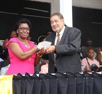 Celia Archibald receives an award from His Honour Eustace John Deputy Governor General for her services in Education