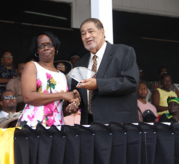Leonie Dasent receives an award from His Honour Eustace John Deputy Governor General for her services in Education
