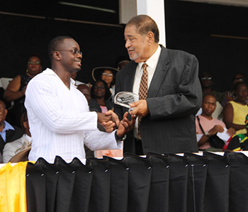 Didier Rohan receives an award on behalf of Lornette Manners from His Honour Eustace John Deputy Governor General for her services in Education