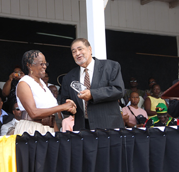 Hyleta Liburd receives an award from His Honour Eustace John Deputy Governor General for services in Education