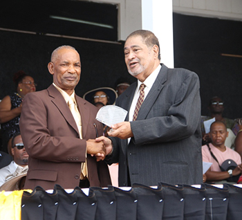 Aubrey Jones receives an award from His Honour Eustace John Deputy Governor General for his services in Industry and Commerce