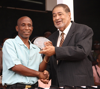 Brem Liburd receives an award from His Honour Eustace John Deputy Governor General for his services in Sports