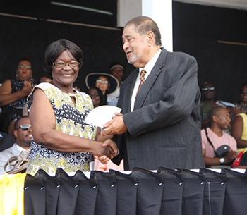Sylvia Jones receives an award from His Honour Eustace John Deputy Governor General for her services in Agriculture