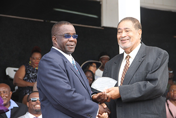 Livingstone Lawrence receives an award from His Honour Eustace John Deputy Governor General for his services in Sports