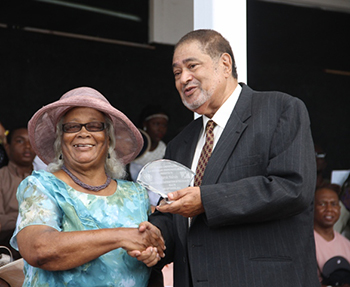 Norah Mulrain receives an award from His Honour Eustace John Deputy Governor General for her services in Health