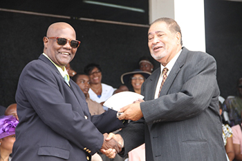Tyrone O'Flaherty receives an award from His Honour Eustace John Deputy Governor General for his services in Culture