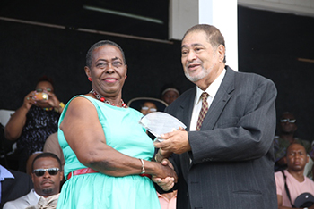 Lornette Thompson receives an award from His Honour Eustace John Deputy Governor General for her services in Public Service