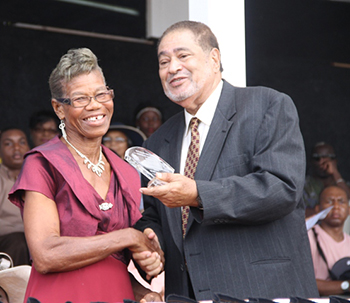 Myrna Webbe receives an award from His Honour Eustace John Deputy Governor General for her services in Health